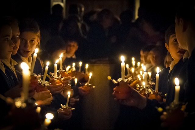 A group of children standing together, holding candles in the darkness