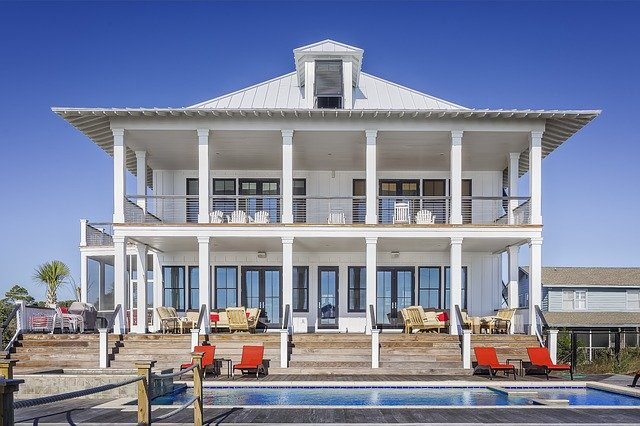 A large home, possibly a vacation home, with a pool and reclining chairs on the deck.