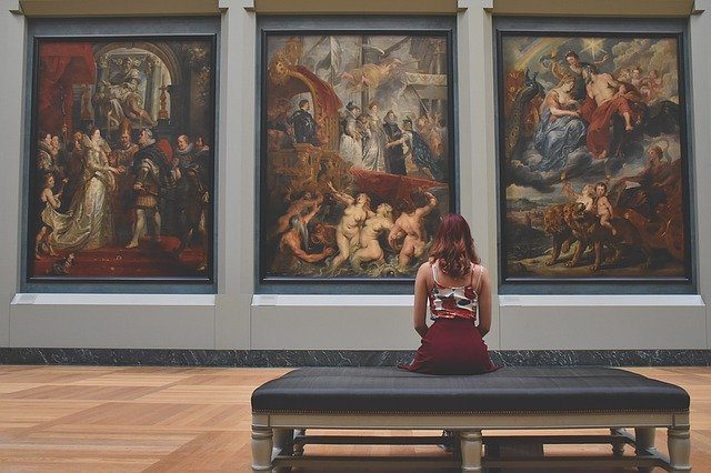 A woman sitting on a bench in a museum, looking at three large framed paintings.