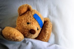 Hurt teddy bear in bed with band aid on his head