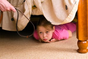 Girl hiding from parent under a bed