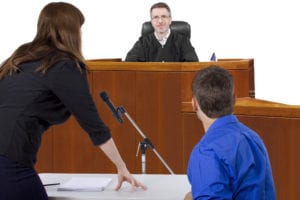 A man sitting before a Judge in court, while his lawyer stands beside him
