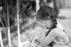 Girl sitting outside with head buried in hands
