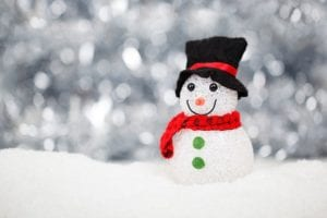a smiling snowman wearing a red scarf and a black hat