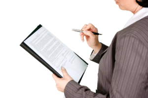 a woman in a suit writing on a clip board