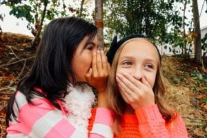 Girls whispering to each other