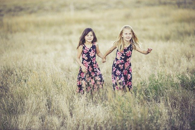 Two little sisters dressed in identical dresses holding hands and running through a field together.