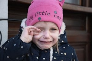 A crying girl wearing a pink hat and a blue coat