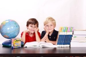 Two young boys with a globe, a stack of books, and crayons