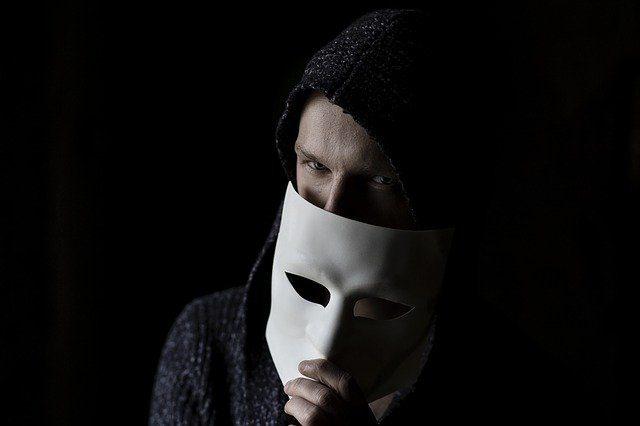 A man against a dark background, holding up a mask that partially covers his face.
