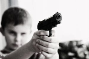A young boy pointing a gun at the viewer