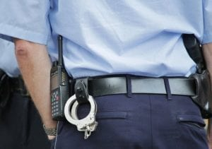 A police officer, close up of the handcuffs on his belt