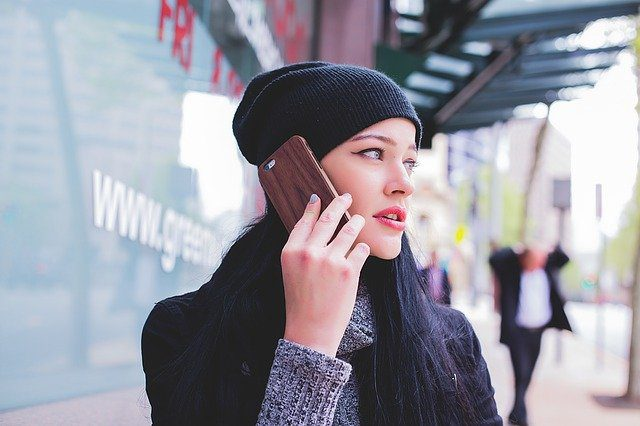 A young woman looking worried and making a phone call.