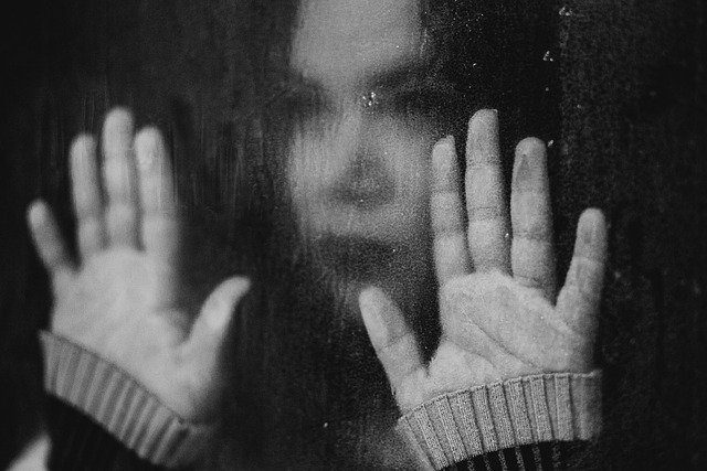 A black and white picture of a woman staring through a rainy window and looking sad.