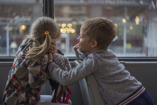 A little boy reaching out to a little girl on the bus. She is hiding her face, as if she may be protecting herself from something.