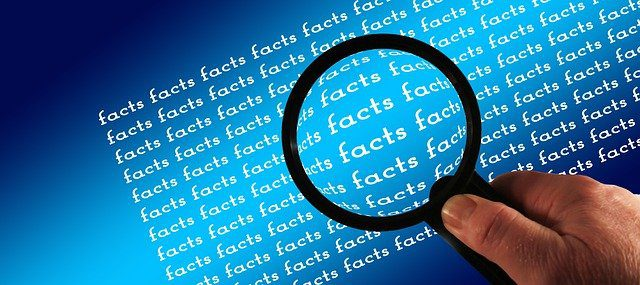 A person's hand holding a magnifying glass over the words 'facts' as if investigating.