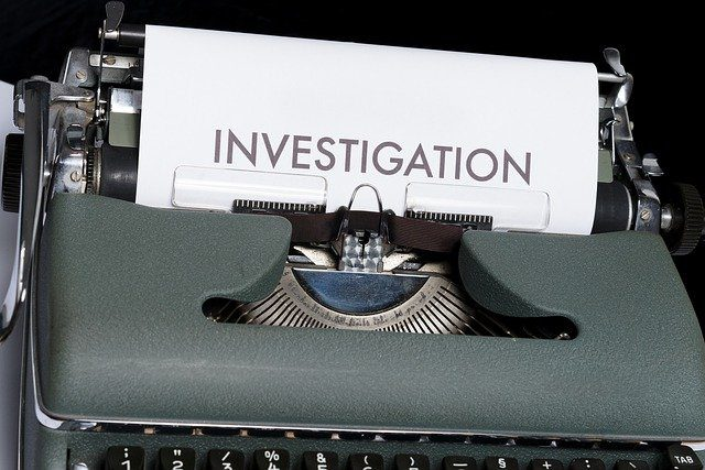 """A close up of a type writer with a paper in it, saying """"investigation"""""""
