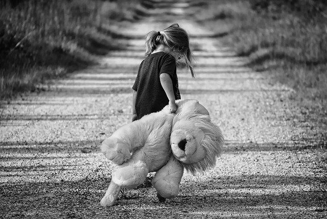 A black and white picture of a little girl, holding a large teddy bear and looking sad, walking away from the camera down a dirt road.