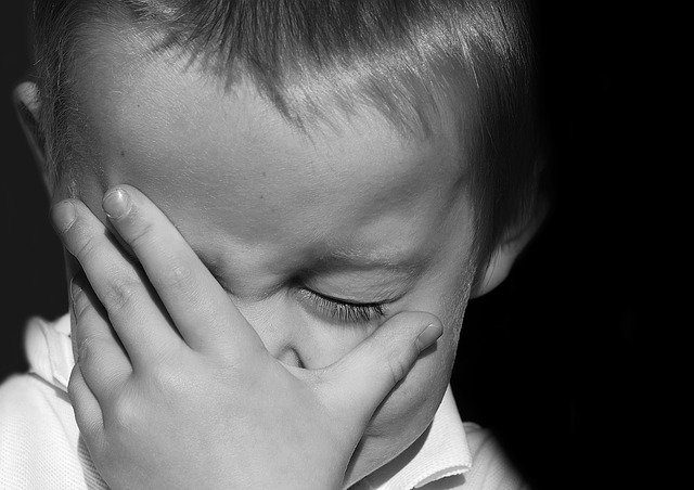 A black and white image of a young boy looking sad with his hand over his face.