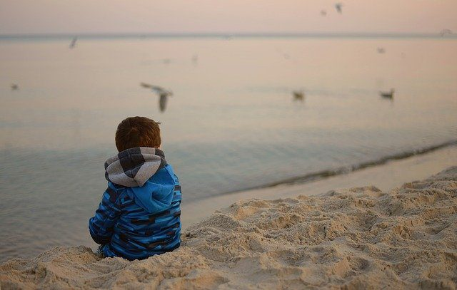 A child sitting alone on the beach with his back to the camera