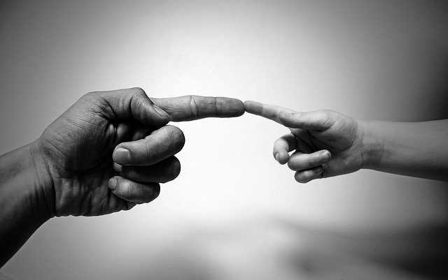 An adults' hand reaching out, and touching a child's fingertip with one finger, similar to Michelangelo's famous painting of God and Adam.