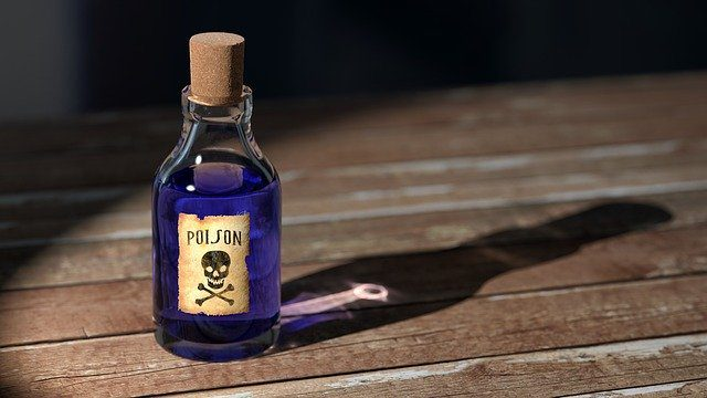 """A bottle of purple poison, labelled """"poison"""" with a skull and crossbones, sitting on an old wooden table."""