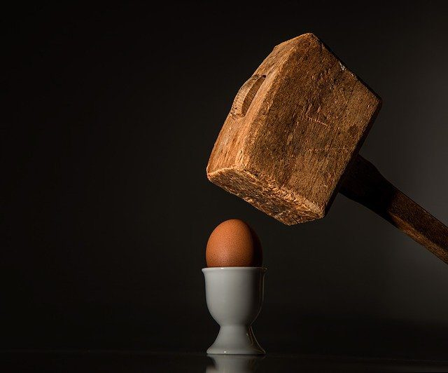 A large wooden hammer coming down to crush a fragile egg, symbolizing a narcissistic parent damaging a child