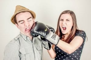 A woman wearing boxing gloves, punching a man in the face