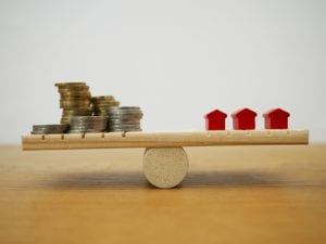 A seesaw with homes on one side and money on the other
