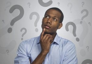 A man looking curious, with question marks all around his head