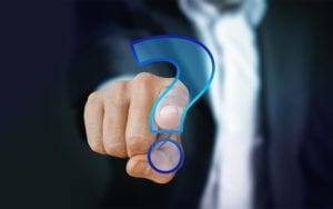 close up of a man reaching out to touch a question mark with his finger