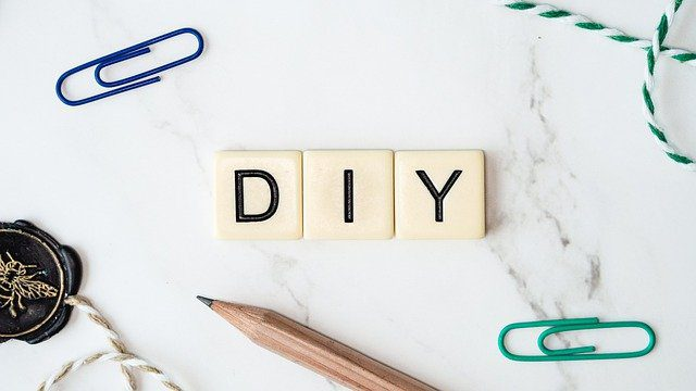 """3 Scrabble tiles spelling out """"DIY"""" surrounded by a pencil and paperclips and a wax stamp."""