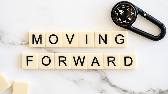 """Scrabble tiles that say """"moving forward' symbolizing the new life to come after a divorce."""