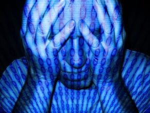 a man with his head in his hands, covered with computer code