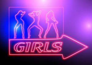 """A flashing neon sign that says """"girls"""" with three female figures"""