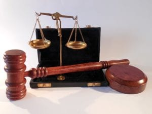 a judge's hammer, and a set of scales, signifying justice