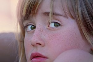 a young girl's face looking worried