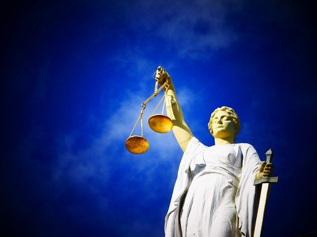 Lady Justice holding up a pair of golden scales in front of a blue sky