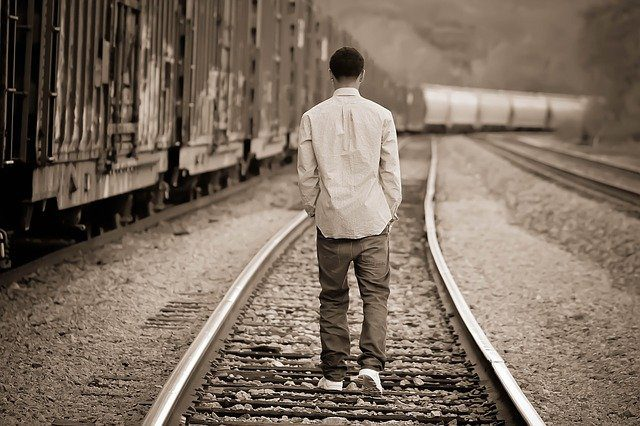 A young teen boy walking away from the camera down a train track. The piture is sepia toned, giving it a slightly sad appearance.